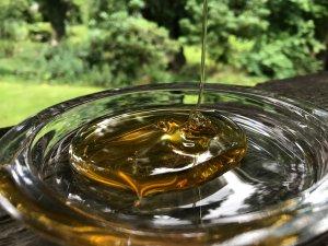 Honig tropft von einem Löffel herunter. Es bildet sich eine Honigpyramide.